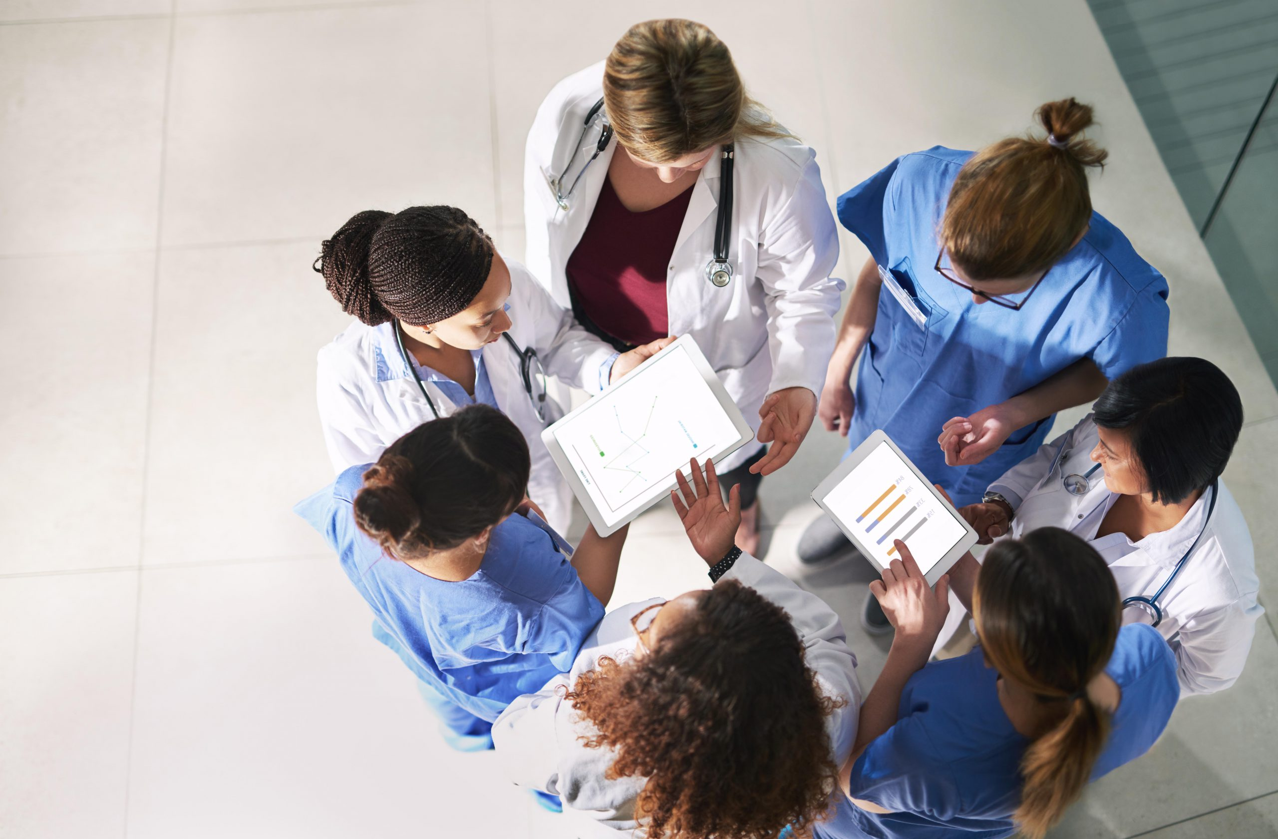 a group of doctors and nurses standing in a circle, discussing their notes